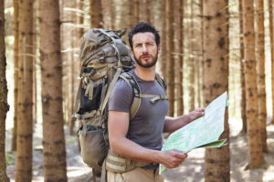 Bearded Man with Backpack and map searching directions in wilderness area.