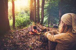 Woman traveler relaxing in forest and cooking food in kettle on fire Travel Lifestyle concept vacations outdoor picnic bivouac in forest