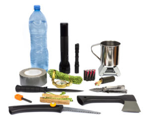 Survival kit with essential emergency supplies to make food and start a fire.