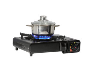 Metal pan standing on modern portable gas range with flame. Isolated on white background with clipping path