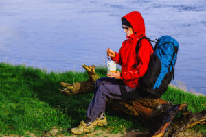 Backpacker eating freeze dried food during resting, sitting on a log near the river. Hiking with backpack